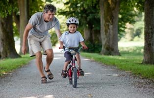 Child riding a bike with his father